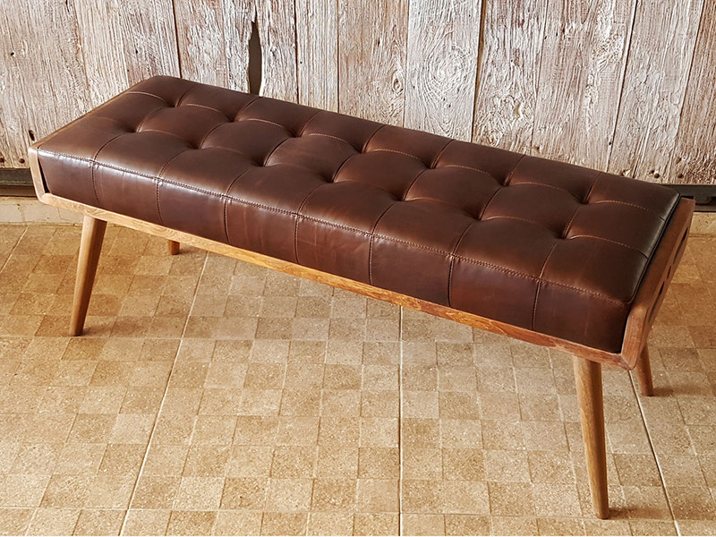 Luxurious and plush buttoned leather bench seat with solid teak frame. Angle view 2