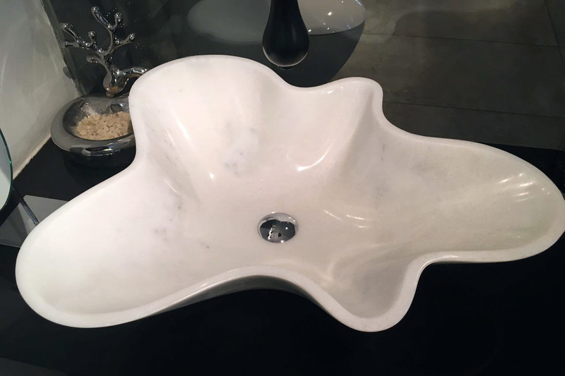 The elegant and fun solid marble Amoeba handbasin in white, installed.