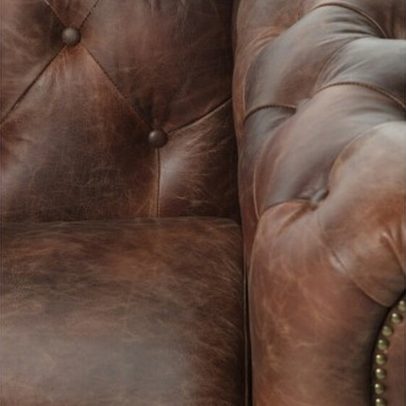 The Eastside leather Chesterfield 4 seater sofa is inspired by iconic British design, for timeless style. Upholstered in distressed leather, featuring diamond buttoning, brass stud detailing, high rolled arms and turned timber legs. Close up