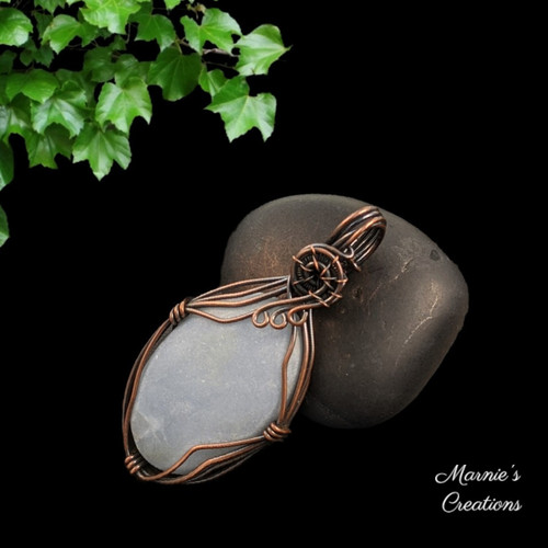Copper wire wrapped pendant with a light blue angelite cabochon