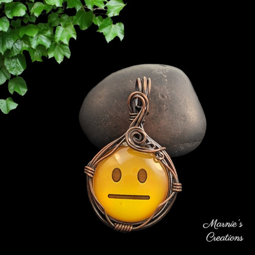 Copper wire wrapped pendant with a glass cabochon showing a yellow emoji with a straight mouth