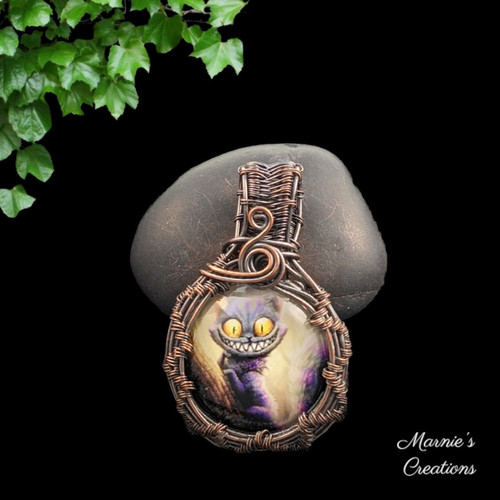 Copper wire wrapped pendant with a glass cabochon showing a cat with a smiling face