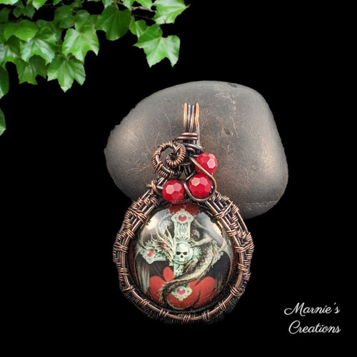Copper wire wrapped pendant with a glass cabochon showing an image of a dragon and skull, accented with faceted glass red beads