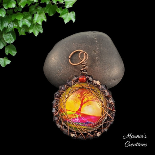 Copper wire wrapped pendant with a glass cabochon showing an image of a pink tree against a yellow background surrounded by purple bicone crystals and accented with a red bead