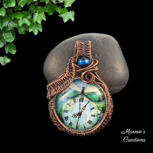 Copper wire wrapped pendant with a glass cabochon showing an image of a clock and a dragonfly, accented with a blue glass bead