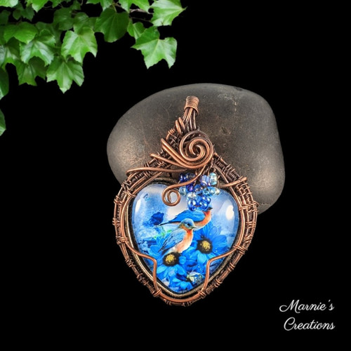Copper wire wrapped pendant with a glass cabochon depicting blue birds and accented with blue glass seed beads