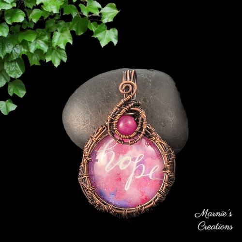 Copper wire wrapped pendant with a glass cabochon depicting the word hope on a pink background and accented with a pink glass bead