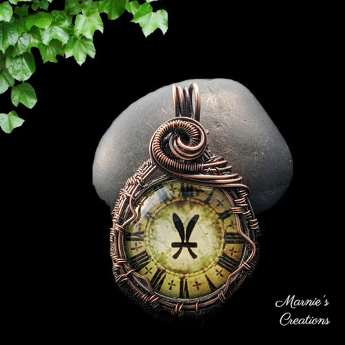 Copper wire wrapped pendant with a glass cabochon depicting the Pisces symbol