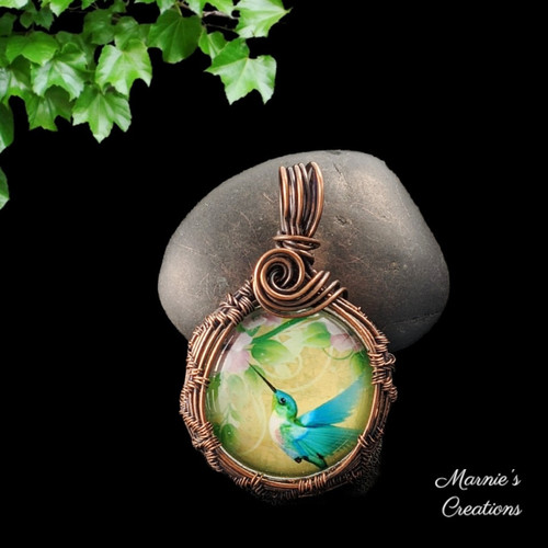 Copper wire wrapped pendant with a glass cabochon depicting a hummingbird