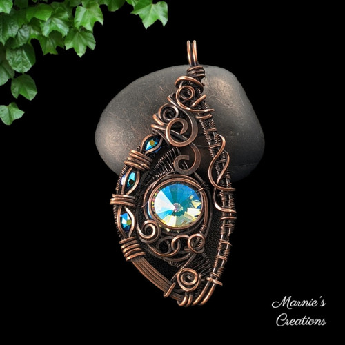 Copper wire wrapped pendant with a Rivoli center and channel set flat back rhinestone accents