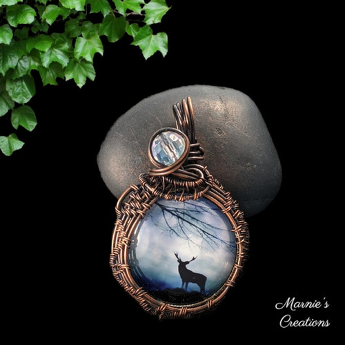 Copper wire wrapped pendant with a glass cabochon depicting a moose with a clear glass bead accent