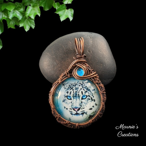 Copper wire wrapped pendant with a glass cabochon depicting a white leopard and accented with a blue flat back rhinestone