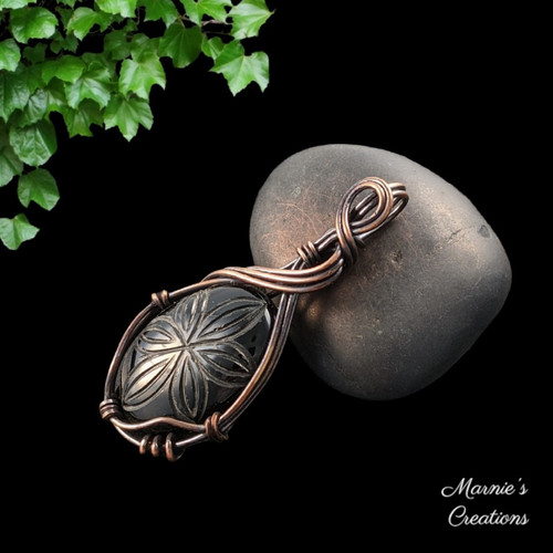 Copper wire wrapped pendant with a flower carved black onyx cabochon