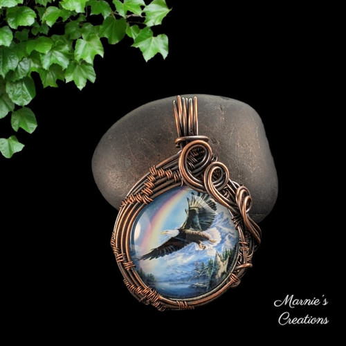 Copper wire wrapped pendant with a glass cabochon depicting an eagle and a rainbow