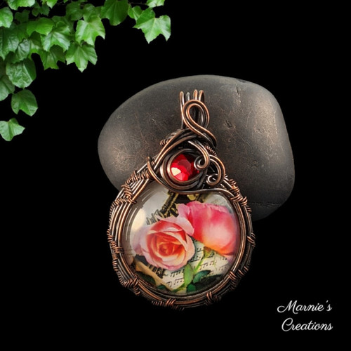 Copper wire wrapped pendant with a glass cabochon depicting pink roses and accented with a red glass bead