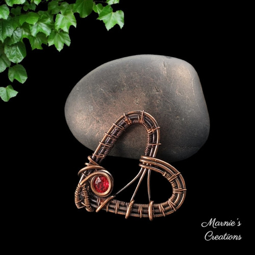 Copper wire weaved heart shaped pendant with a red flatback rhinestone