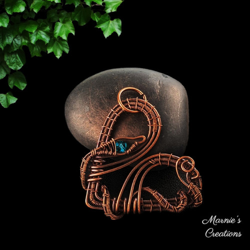 Copper wire weaved heart shaped pendant with a snake figure, green crystal bead for an eye
