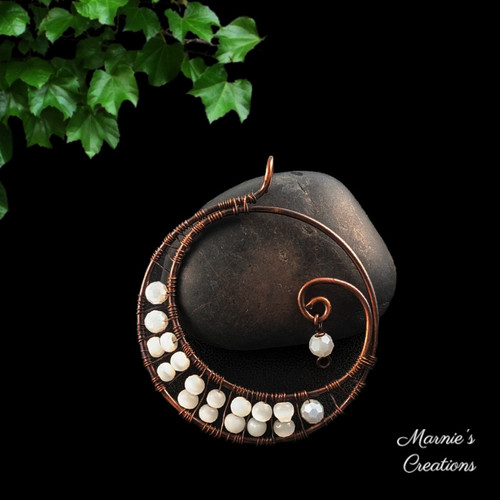 Copper moon shaped pendant with white glass beads
