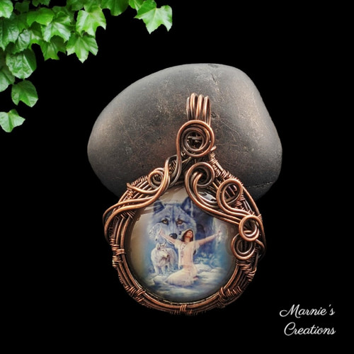 Copper wire pendant with a glass cabochon depicting a female with wolves