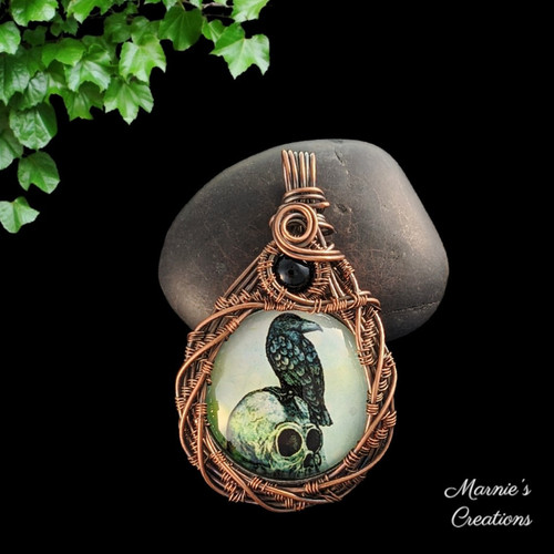 Copper wire wrapped pendant with a glass cabochon depicting a raven on a skull, accented with a black glass bead