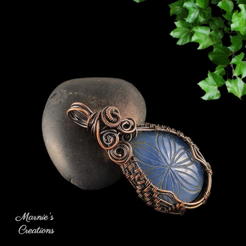 Copper wire wrapped pendant with a flower carved blue onyx cabochon