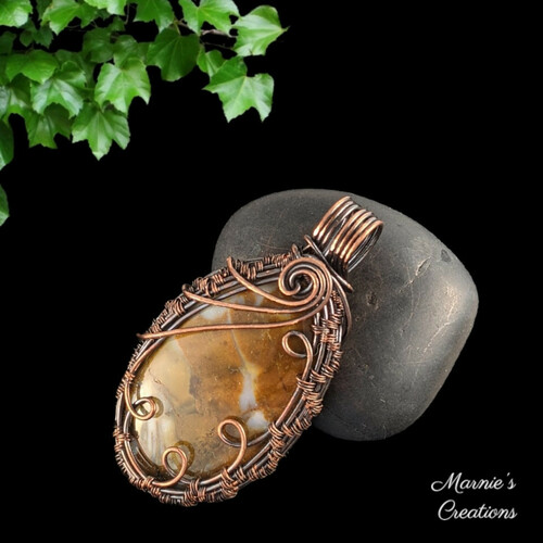 Copper wire wrapped pendant with a rust brown agate cabochon