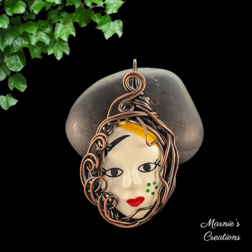 Copper wire wrapped pendant with a resin cabochon depicting a female face