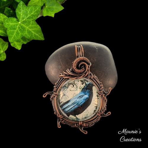 Copper wire wrapped pendant with a glass cabochon depicting a raven
