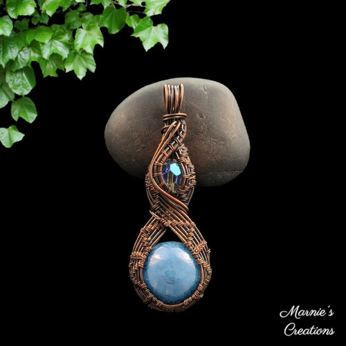 Copper wire wrapped pendant with a blue Czech glass cabochon and a faceted glass bead accent