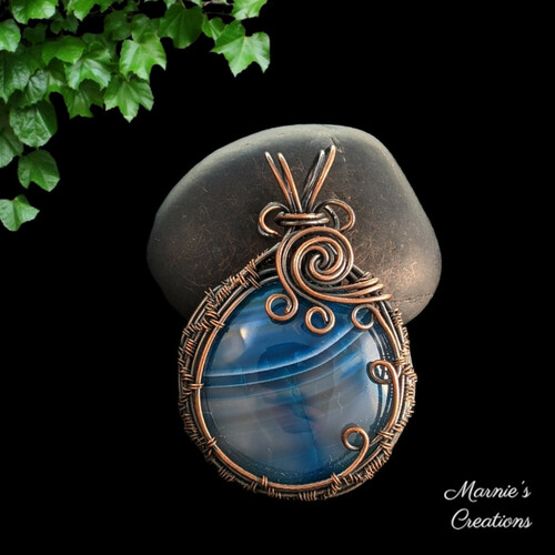 Copper wire wrapped pendant with a blue striped agate cabochon