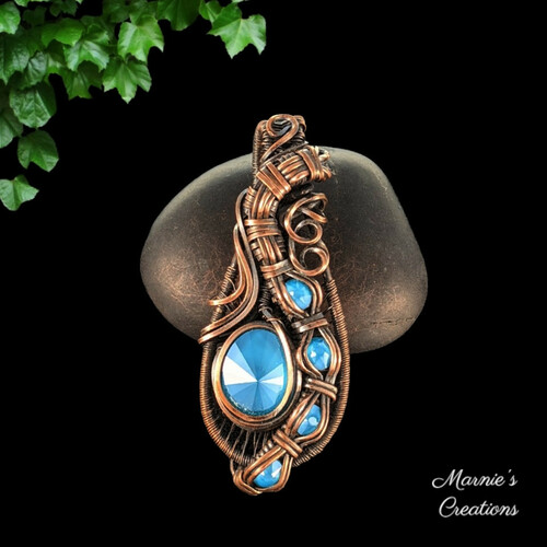 Copper wire wrapped pendant with a blue rhinestone and blue flat back cabochon accents