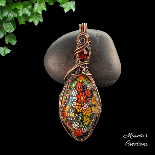 Copper wire wrapped pendant with a millefiori cabochon and a faceted red glass bead accent