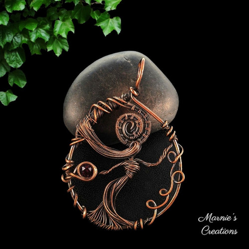 Copper wire pendant with a female shape and a purple flat back cabochon