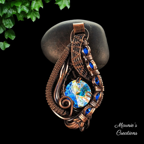 Copper wire wrapped pendant with a multi-colored Rivoli crystal and blue flat back cabochons