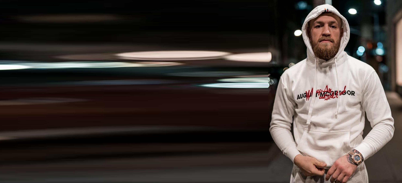 Conor McGregor wearing white Whoop Ass hoodie.