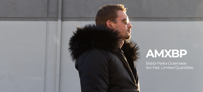 Model wearing Bobbi Parka faux fur hooded bomber jacket in black.