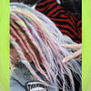 Caitlin wearing synthetic dreads in Bright Lilac, Candyfloss, Light Denim, Mojito, Icy Blue, and Lime Delight