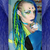 Amber Blue wearing synthetic dreads made from 1 Black, Lime Green, Petrol Ombré, Sky Blue, Space Cadet, and Turquoise kanekalon