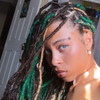 Raine wearing faux locs made from marley braid in 6 Chestnut Brown, 27 Strawberry Blond, and 1B Off Black/Emerald Green Mix