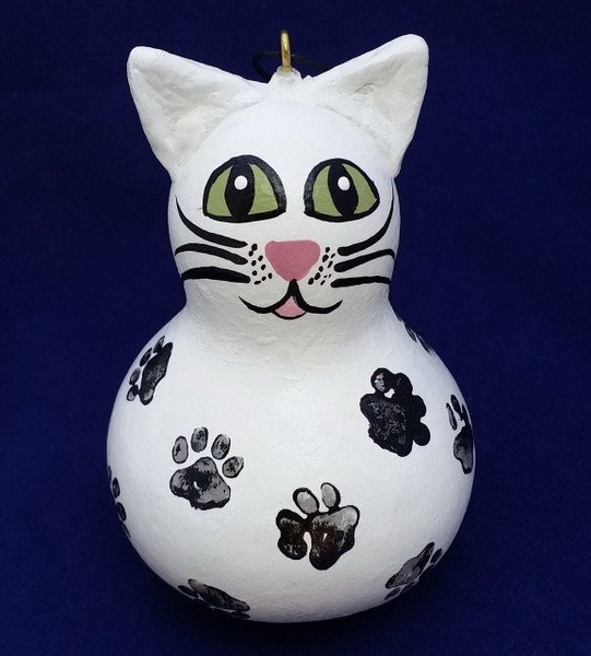 This is a white cat with black paw prints.