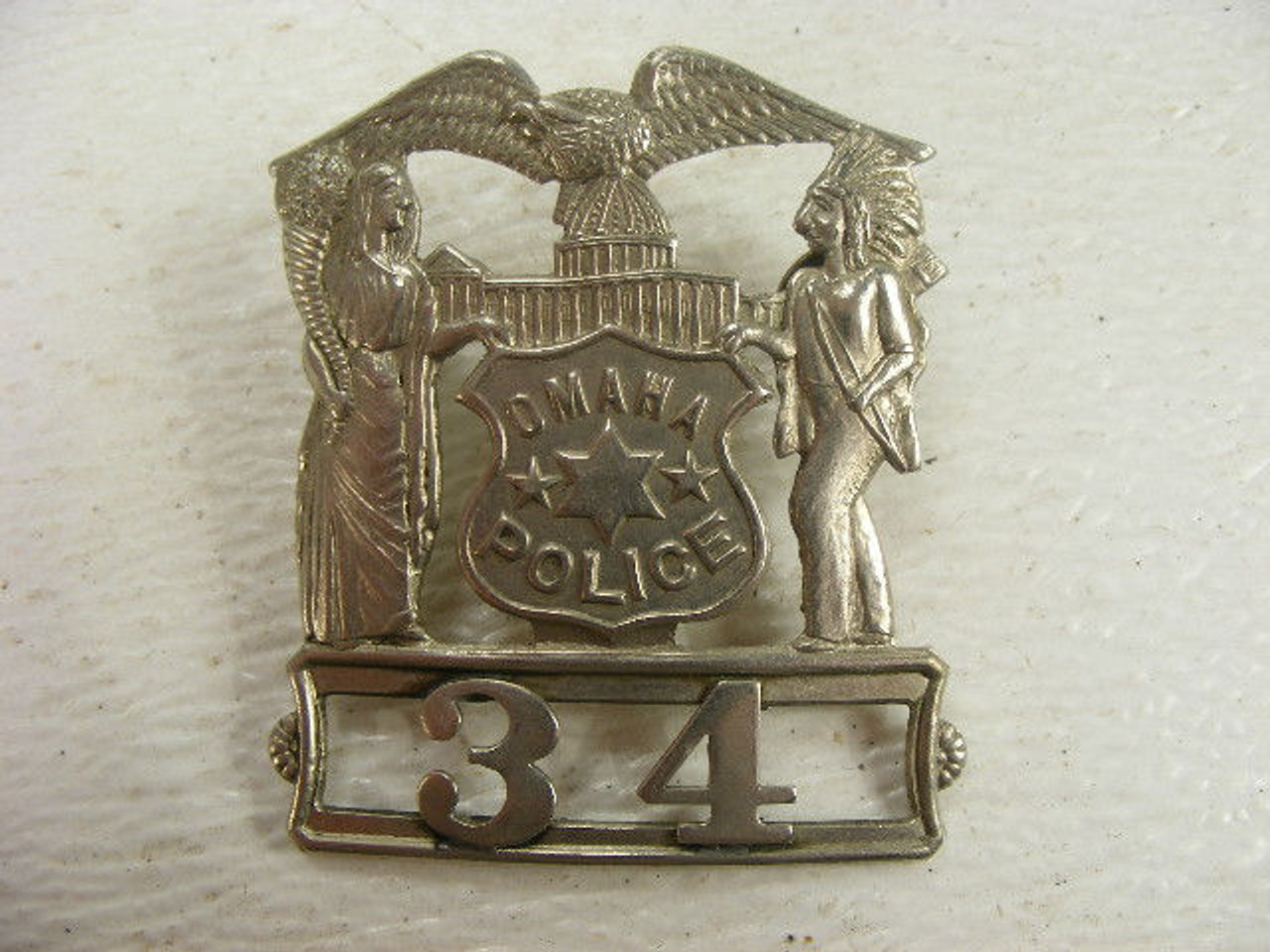 An old Omaha Police badge depicting Native Americans and an