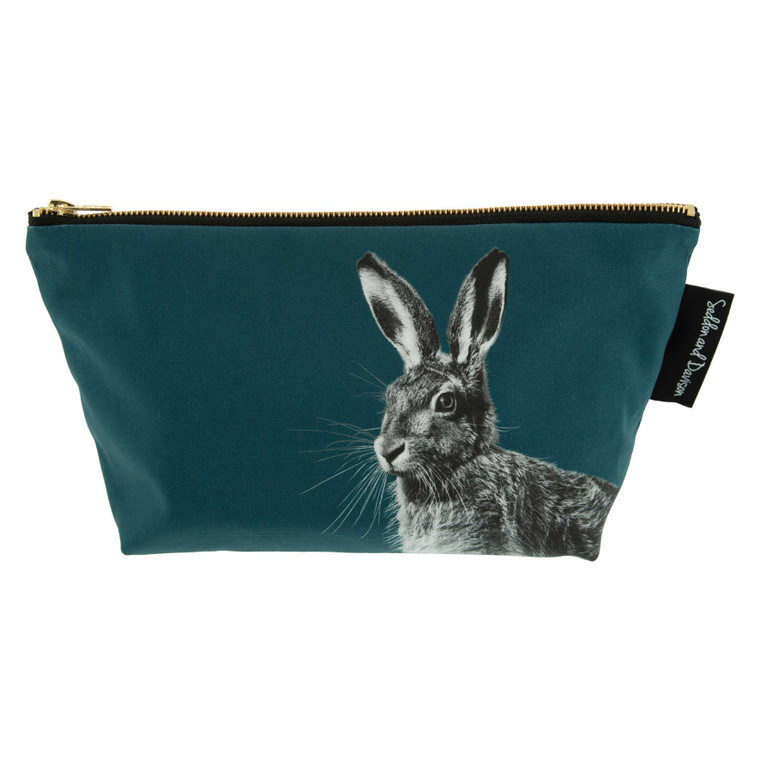 A large cosmetic bag in rich teal green with a black and white photo of a hare starting in the bottom right corner and covering approximately half of the bag. The top of the bag is slightly wider than the bottom and it is free standing. There is a label on the right with the company name. The background in this image is plain white.