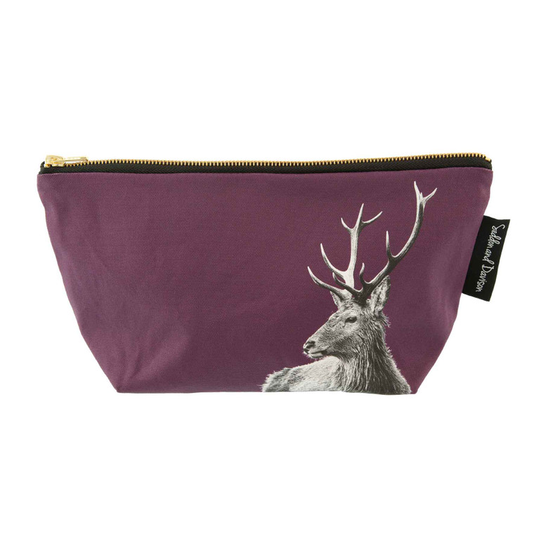 A large cosmetic bag in rich claret purple with a black and white photo of the top portion of a highland stag starting in the bottom right corner and covering approximately half of the bag. The top of the bag is slightly wider than the bottom and it is free standing. There is a label on the right with the company name. The background in this image is plain white.
