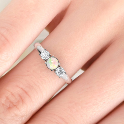 opal and diamond ring on finger