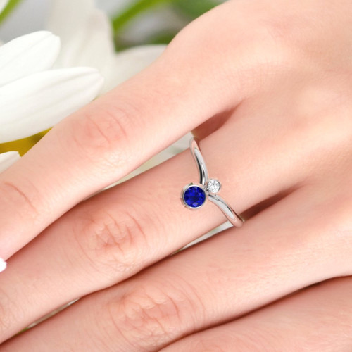 white gold sapphire and diamond ring on a finger