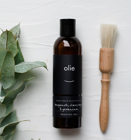 Olie shaving gel in bottle laying flat with wooden shave brush