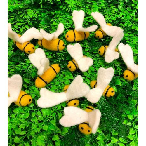 a group of  felt bees on green grass
