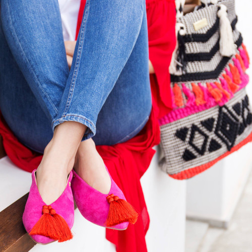 hot pink flat shoe with red tassel at front.
