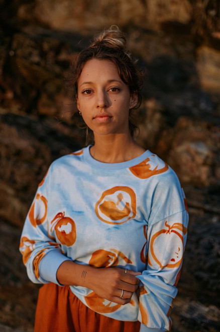 Model wearing Fuseta sweater featuring pale blue and rust patterned ethical  fabric. Designed in Australia.