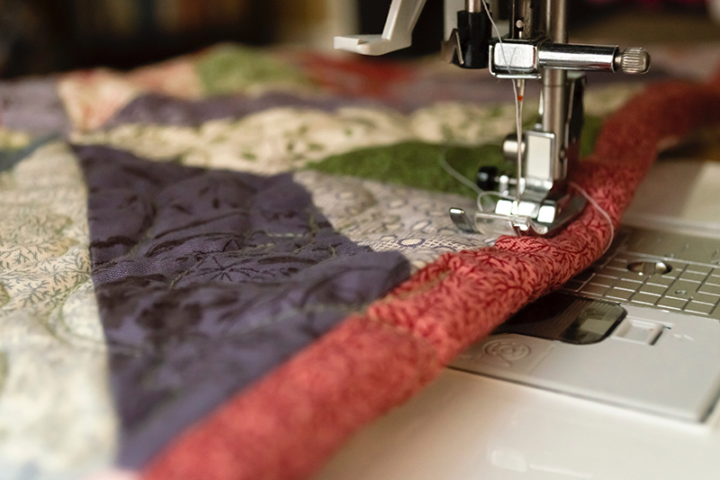 An example of using a sewing machine to make a quilt from on online quilt store kit